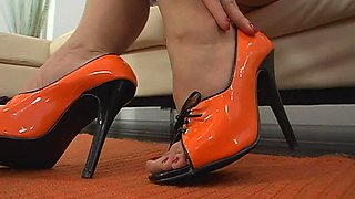 A girl takes off her orange shoes and gives a nice footjob