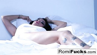 Solo fun on the bed with the busty pornstar Romi Rain