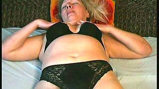 Blonde mature woman in black lingerie and stockings plays on the bed