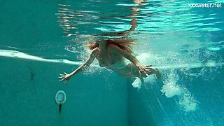 Attractive slender beauty is a really good swimmer and stripper