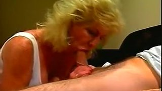 Mature blonde white lady blowing dick of a young man on the couch