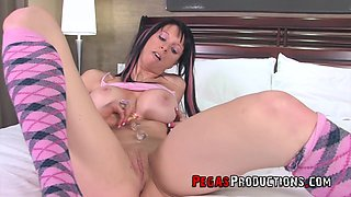 Peaches Gold pleases her shaved pussy on the bed using her fingers and sex toys