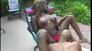 Enchanting ebony with big tits giving her guy blowjob outdoor