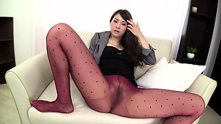 Seductive Oriental babe in pantyhose gives a hot footjob