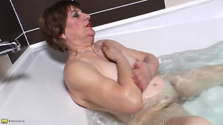 Attractive matured granny fingering her pussy immensely in the bath tab